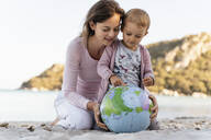 Mother and little daughter looking together at Earth beach ball - DIGF08846