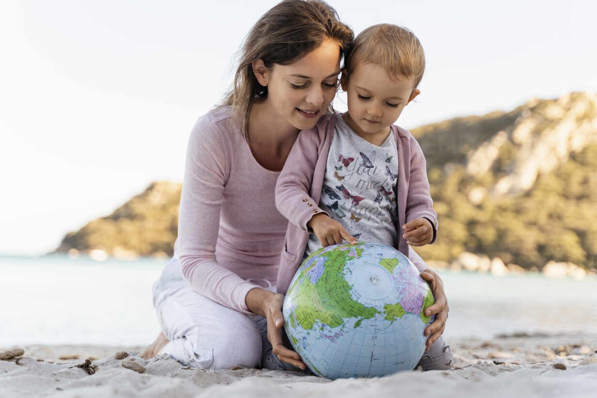 Mother and little daughter looking together at Earth beach ball - DIGF08846 - Daniel Ingold/Westend61