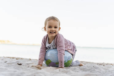Portrait of happy little girl playing with  Earth beach ball - DIGF08849
