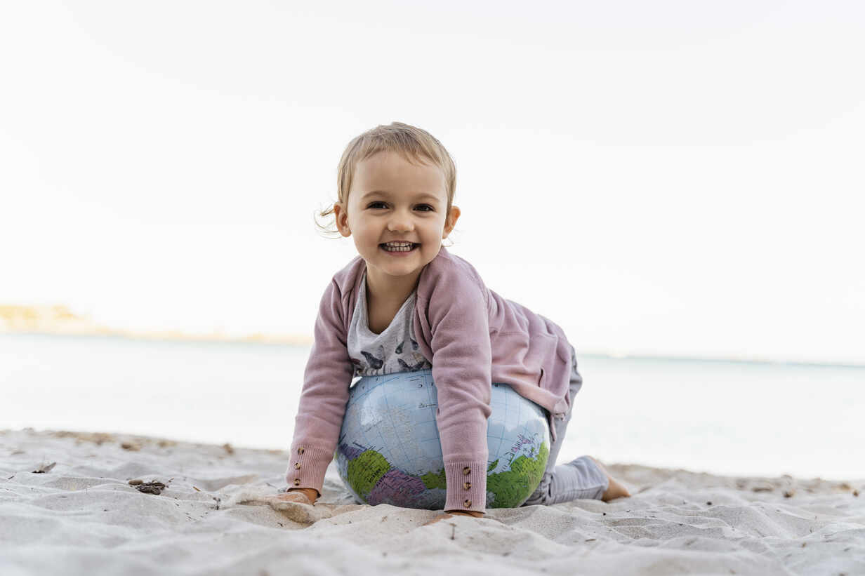 Portrait of happy little girl playing with  Earth beach ball - DIGF08849 - Daniel Ingold/Westend61