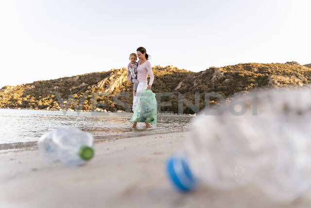 Woman  carrying little daughter on her arm collecting empty plastic bottles at seashore - DIGF08858 - Daniel Ingold/Westend61