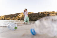 Woman  carrying little daughter on her arm collecting empty plastic bottles at seashore - DIGF08858