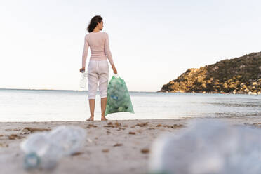 Back view of woman standing on the beach with bin bag of collected empty plastic bottles - DIGF08864
