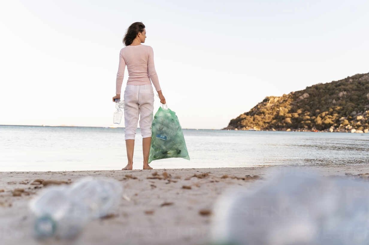 Back view of woman standing on the beach with bin bag of collected empty plastic bottles - DIGF08864 - Daniel Ingold/Westend61