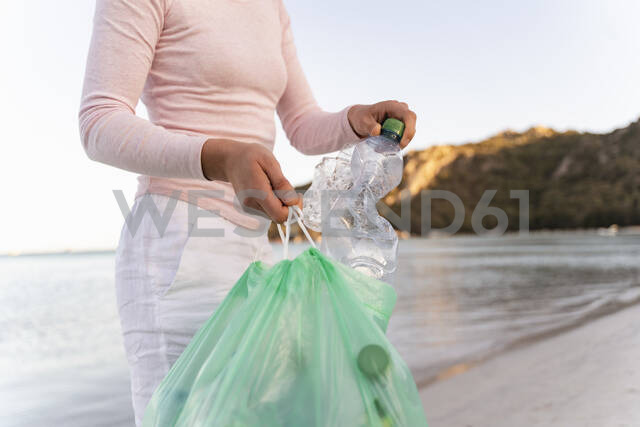 Woman collecting empty plastic bottles  on the beach - DIGF08867 - Daniel Ingold/Westend61