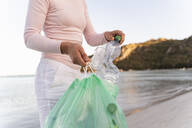 Woman collecting empty plastic bottles  on the beach - DIGF08867