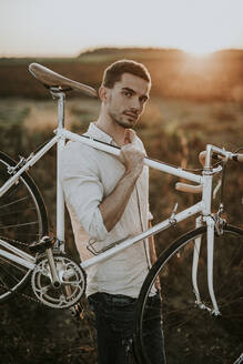 Pensive young man carrying a racing cycle in the sunshine - MKF00011