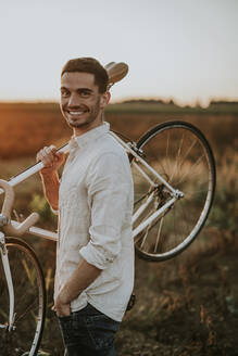 Portrait of a smiling young man carrying a racing cycle in the sunshine - MKF00014