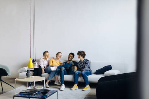 Happy young people sitting together on couch sharing smartphone - SODF00150