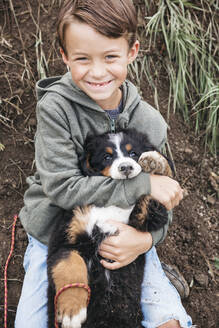 Boy playing with his Bernese mountain dog in the garden - HMEF00670