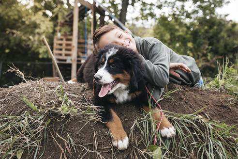 Boy playing with his Bernese mountain dog in the garden - HMEF00673