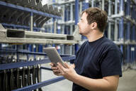 Worker using tablet in factory warehouse - WESTF24270