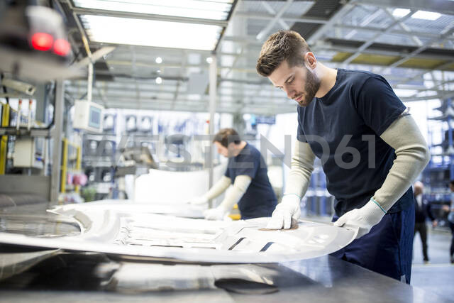 Two colleagues wiping component in car factory - WESTF24282 - Fotoagentur WESTEND61/Westend61