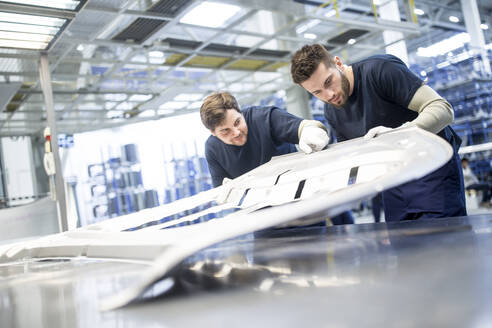 Two colleagues examining component in car factory - WESTF24285