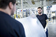 Two colleagues carrying bonnet in car factory - WESTF24288