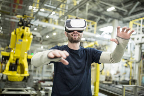 Man wearing VR glasses in modern factory - WESTF24309