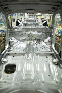 Two colleagues working in modern car factory - WESTF24333