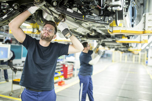 Two colleagues working at car underbody in modern factory - WESTF24342