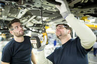 Two colleagues working at car underbody in modern factory - WESTF24345