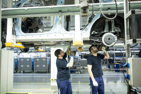 Two colleagues working at car underbody in modern factory - WESTF24348
