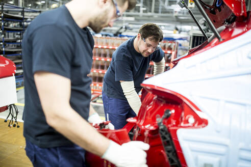 Two colleagues working in modern car factory - WESTF24354