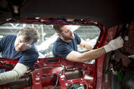 Two colleagues working at bodywork in modern car factory - WESTF24360