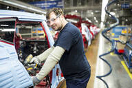Portrait of confident man working in modern car factory - WESTF24366