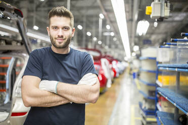 Portrait of confident worker in modern car factory - WESTF24372