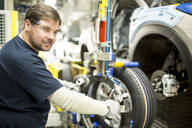 Portrait of confident worker in modern car factory - WESTF24381