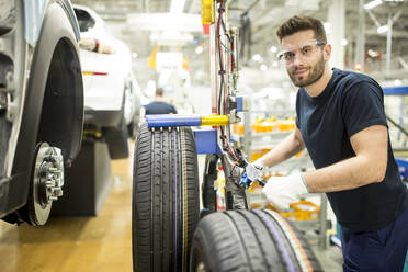 Portrait of confident man working in modern car factory - WESTF24384