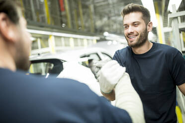 Two colleagues shaking hands in modern car factory - WESTF24390