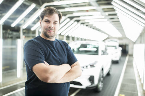 Portrait of confident worker in modern car factory - WESTF24399