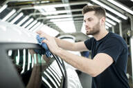 Man working in modern car factory wiping finished car - WESTF24402