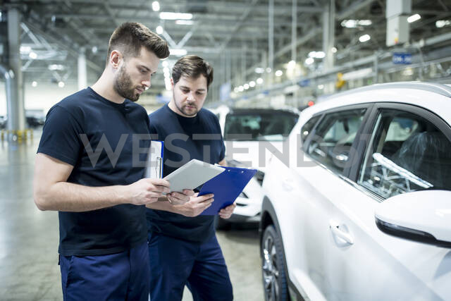Two colleagues working in modern car factory using clipboard and tablet - WESTF24411 - Fotoagentur WESTEND61/Westend61