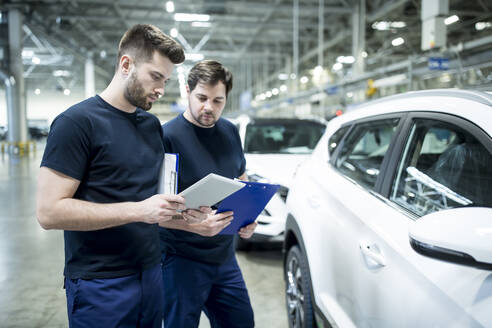 Two colleagues working in modern car factory using clipboard and tablet - WESTF24411