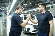 Two colleagues shaking hands in modern car factory - WESTF24414