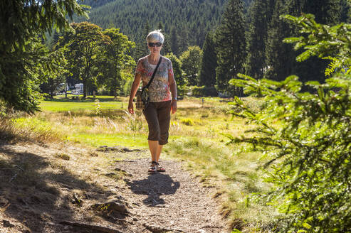 Senior woman hiking on forest path, Oberhof, Thuringia, Germany - FRF00880