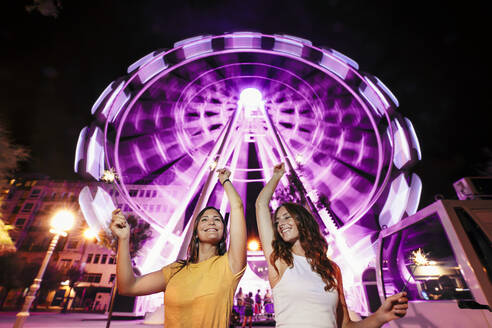 Two friends with sparkles in front of illuminated big wheel at night - MTBF00085