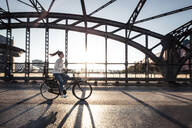 Young cyclist on a bridge at sunset - WFF00143