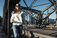 Young woman with sunglasses on a bridge in the evening light - WFF00149