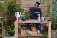 Young man using digital tablet on his terrace while gardening - IGGF01377