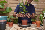 Young man repotting a plant on his terrace - IGGF01380