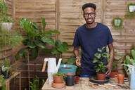Portrait of a smiling young man repotting a plant on his terrace - IGGF01383