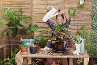 Portrait of a smiling young woman gardening on her terrace - IGGF01392