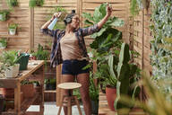 Happy young woman dancing on her terrace while gardening - IGGF01395