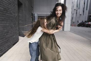 Girl hugging her smiling mother - EYAF00633