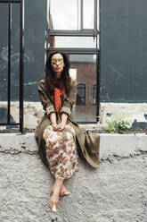 Portrait of stylish woman wearing mirrored sunglasses and red scarf sitting on a wall - EYAF00636