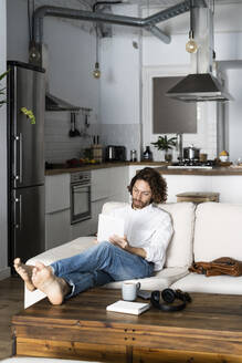 Relaxed man sitting on couch at home using tablet - GIOF07471