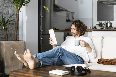 Relaxed man sitting on couch at home using tablet - GIOF07474