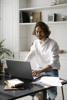 Portrait of confident man sitting at table at home using laptop - GIOF07486